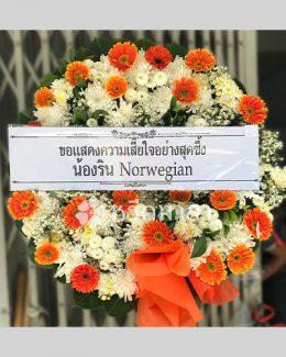 พวงหรีดจัดด้วยดอกไม้สดสีส้มและขาว จัดเป็นทรงกลมขนาดกลาง