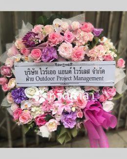 พวงหรีดจัดด้วยดอกไม้ประดิษฐ์ ใช้ดอกไม้โทนชมพู ม่วง และขาว