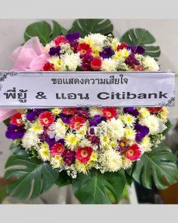พวงหรีดดอกไม้สด จัดเป็นทรงกลม โทนสีม่วงและชมพู จัดอย่างประณีต