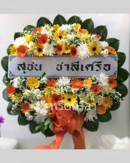 ดอกไม้สดนำมาจัดเป็นพวงหรีดโทนสีสดใสจากดอกเยอบีร่าและเบญจมาศ