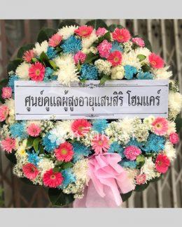 พวงหรีดจัดด้วยดอกไม้สดสีฟ้า ชมพู และขาว คัดดอกไม้มาแล้วอย่างดี
