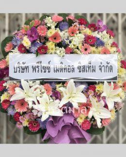พวงหรีดดอกไม้สดคละสี เน้นสีโทนม่วงชมพู โดดเด่นด้วยดอกลิลลี่ขาว