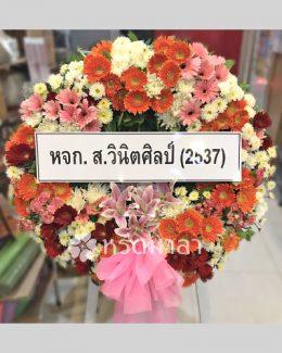 ดอกไม้สดสีส้ม ขาว และชมพู จัดเป็นพวงหรีดสีสันสดใส ให้ความรู้สึกสดชื่น