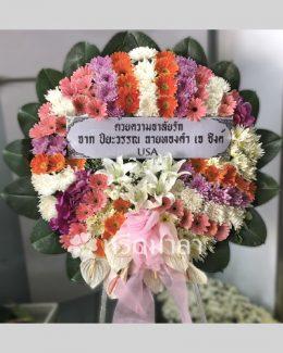 พวงหรีดดอกไม้สดจัดโดยเน้นสีม่วง ส้ม ชมพู และขาว สลับสีกันอย่างลงตัว